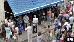 Decenas de personas hacen cola frente a una Casa de Cambio (CADECA) para cambiar sus dólares por pesos cubanos, hoy miércoles 27 de octubre, en La Habana (Cuba). Las CADECAS continúan recibiendo una avalancha de cubanos, muchos de ellos ancianos, deseosos
