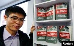 """Shin Dong-hyuk posa con su libro """"Escape del Campamento 14""""."""