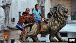 Varios niños juegan sobre uno de los leones del Paseo del Prado de La Habana (Cuba)