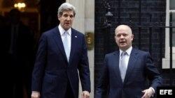 El ministro de Exteriores británico, William Hague (dcha), conversa con el secretario de Estado de EE. UU., John Kerry (izq), a las puertas del número 10 de Downing Street tras una reunión mantenida por ambos responsables hoy, lunes 25 de febrero de 2013.