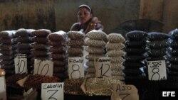 Una mujer vende frijoles en un mercado.