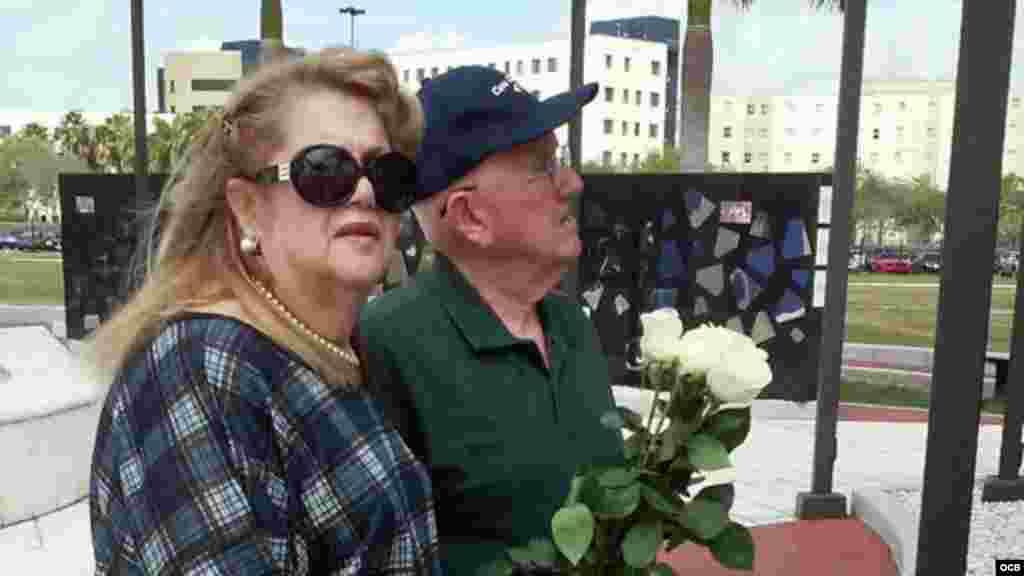 Graciela y Emilio Vázquez colocan flores blancas en el primer aniversario del Memorial Cubano.
