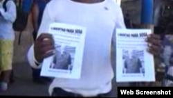 Reporta Cuba. Un activista portando proclamas por la libertad de un preso político.
