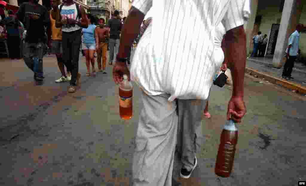 Un hombre camina esta tarde con dos botellas de cerveza por la calle Galiano del municipio Centro Habana, Cuba.