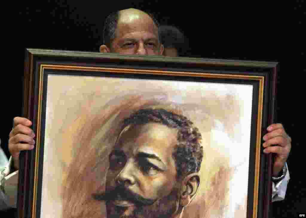 Luis Guillermo Solís (c) sostiene un retrato del prócer cubano Antonio Maceo.
