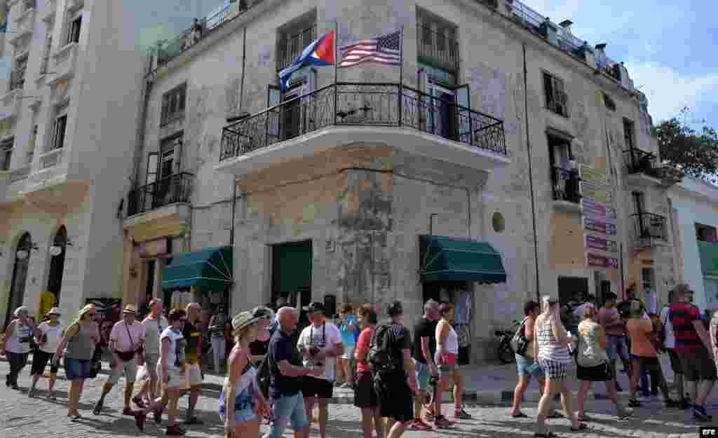 Varios turistas caminan junto a un edificio con las banderas de Cuba y Estados Unidos hoy, jueves 17 de marzo de 2016.