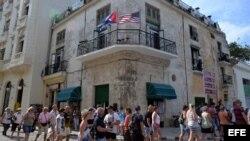 Varios turistas caminan junto a un edificio con las banderas de Cuba y Estados Unidos, en La Habana.