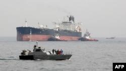 Una lancha militar iraní patrulla las aguas mientras un petrolero se prepara para atracar en las instalaciones petroleras en la isla de Khark, en Irán.
