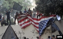 Manifestantes arrancan la bandera de la Embajada de Estados Unidos en El Cairo.