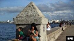 Una joven se conecta a internet en el muro del Malecón, en La Habana.