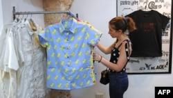 Clienta valorando la ropa de tienda Clandestina, uno de los negocios privados más exitosos de la isla.