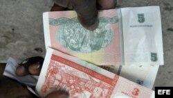 Una persona muestra la nueva serie de billetes de pesos convertibles cubanos.