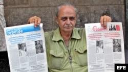 """Un vendedor de periódicos en La Habana muestra el diario oficial """"Granma"""" y """"Juventud Rebelde"""", con la misma portada."""