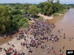 Vista aérea de la carava de migrantes cruzando el río Suchiate, en Guatemala, hacia Ciudad Hidalgo, en México.