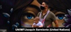 Un padre con su hijo durante la pandemia COVID Description: Un padre con su hijo durante la pandemia COVID en la comuna 13 de Medellin, en Colombia. Foto: UN/IMF/Joaquin Sarmiento.