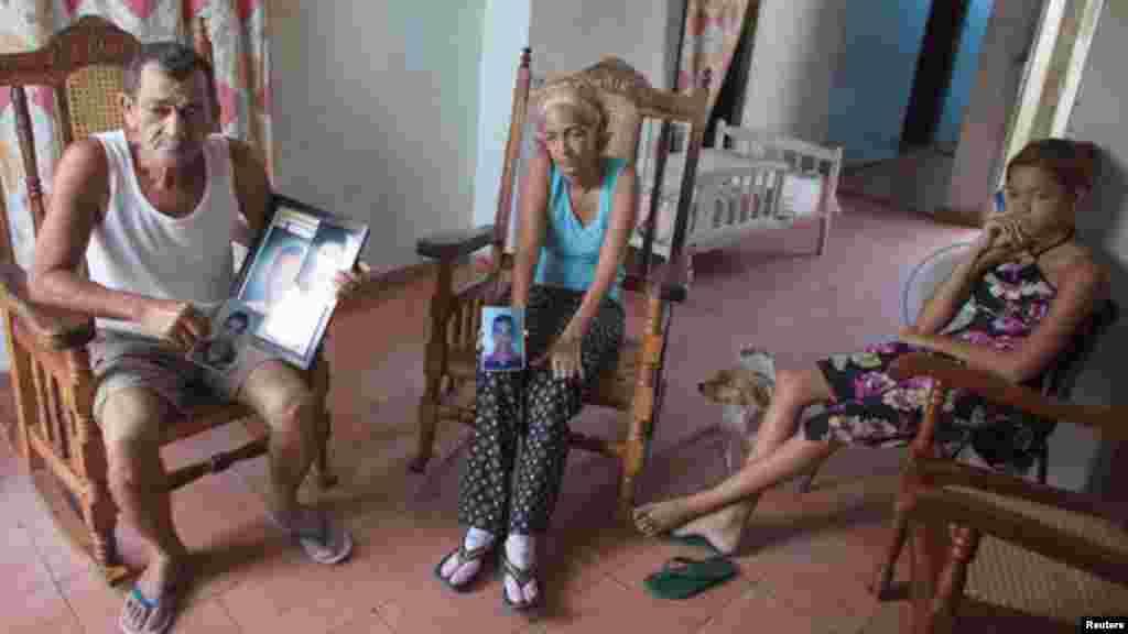 Joaquín de La Paz, mecánico (izquierda) y su esposa Xiumara Milán Montero (centro), sentados con uno de sus nietos, sostienen fotografías de dos de sus hijos y dos de sus otros nietos que recientemente murieron tratando de llegar a Honduras en un improvisado barco.