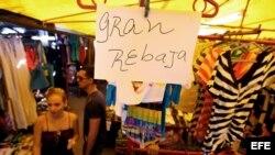 Detalle de un letrero que anuncia rebajas en una tienda de ropa importada ofertada por comerciantes privados.