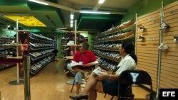 Dos empleadas leen el periódico en una tienda de calzado deportivo ubicada en el Centro Comercial Carlos III.