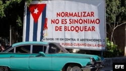 Un auto pasa junto a un cartel alusivo al embargo estadounidense a Cuba.