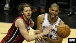El jugador de los Spurs Tim Duncan (d) disputa una bola ante Mike Miller (i) de los Heat , durante el partido de las Finales de la NBA que se disputa en el AT&T Center de San Antonio, Texas, EE.UU.