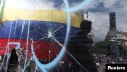 La bandera venezolana es vista a través de un cristal roto durante una manifestación contra Nicolás Maduro en Caracas. (Archivo)