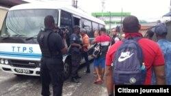 Autoridades migratorias de Trinidad Tobago desalojan en autobuses a más de 80 cubanos que estaban acampados en protesta frente a la sede local de la ACNUR (Jacqueline Vera)