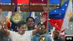 El campeón del mundo del peso pluma, el filipino Emmanuel 'Manny' Pacquiao, saluda a sus seguidores en Manila, Filipinas (Archivo).