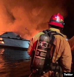 Un rescatista arriba a la escena del incendio, con el bote aún en llamas. (Tomada de Twitter)