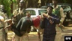 Personal militar de Mali traslada a una mujer herida a su salida del hotel de lujo Radisson Blu en Bamako. EFE