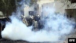 """Agentes de policía antidisturbios egipcios, tratan de protegerse de los gases lacrimógenos lanzados por los manifestantes durante una protesta contra el """"decretazo"""" del presidente egipcio, Mohamed Morsi."""
