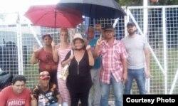 Onelia, al centro con sombrero, posa junto a otros cubanos en Trinidad y Tobago.