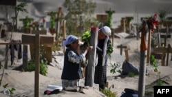 Mujeres uigures decoran una tumba en las afueras de Hotan, en la región de Xinjiang (Foto: AFP).