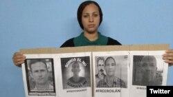 La esposa de José Daniel Ferrer, Nelva Ismarays Ortega, sostiene un cartel exigiendo su liberación.