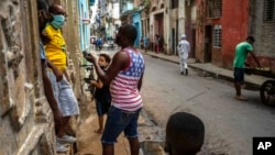 Cubanos conversan protegidos con mascarillas. AP Photo/Ramon Espinosa, File)