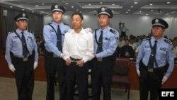 Bo Xilai, esposado, con los puños apretados en una aparente muestra de resistencia, rodeado por dos altos policías que lo sostenían de los hombros y antebrazos.