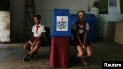 Dos niños custodian la urna en un colegio electoral de La Habana durante el referendo constitucional.