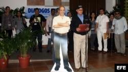 """El guerrillero Rodrigo Granda (d), alias """"Ricardo Téllez"""", lee una declaración junto a una una silueta de cartón a tamaño natural de Simón Trinidad en el Palacio de Convenciones, en La Habana (Cuba)."""