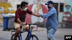 Dos hombres se estrechan la mano en una calle de La Habana, en medio de una ola de contagios de coronavirus. (YAMIL LAGE / AFP)