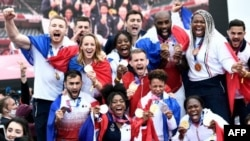 El equipo olímpico de judo francés, medallistas de oro por equipos mixtos, posan mientras celebran su regreso de los Juegos Olímpicos de Tokio 2020 frente a la Torre Eiffel, en París el 2 de agosto de 2021 (Foto de STEPHANE). DE SAKUTIN / AFP)