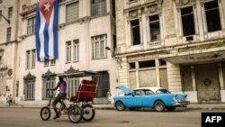 Un bicitaxi y un almendrón circulan por La Habana. (Archivo)
