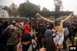 Manifestantes remueven el crucifijo de la Iglesia de la Gratitud Nacional hoy, jueves 9 de junio de 2016, en una protesta de miles de estudiantes.
