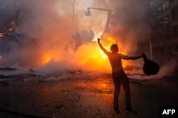 Manifestante en Santiago de Chile festeja la quema de la Iglesia de la Asunción.