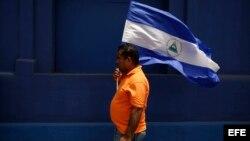 Manifestante enarbola la bandera nicaragüense durante una protesta en Managua. (Archivo)