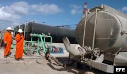 Archivo. Dos obreros trabajan en la planta de Puerto Escondido, una de las plantas de la empresa estatal cubana Cuba Petróleos (CUPET).