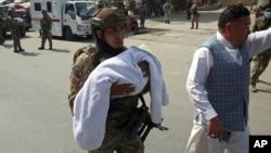Un soldado afgano carga un bebé tras el ataque armado contra la sala de maternidad de un hospital en Kabul, Afganistán, el 21 de mayo del 2020.