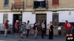 Un grupo de personas hace fila para recibir alimentos distribuidos por la Cruz Roja en Valencia el pasado 20 de abril. JOSE JORDAN / STR / AFP