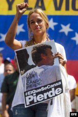 """Lilian Tintori muestra una pancarta con la imagen de su esposo, el líder opositor Leopoldo López, con el mensaje siguiente: """"#el que se cansa pierde""""."""