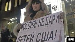 Una mujer protesta en contra de la prohibición de adopción de huérfanos rusos a ciudadanos americanos a las puertas del Consejo de la Federación en Moscú (Rusia). 26 de diciembre de 2012.