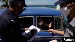 La policía revisa documentos de los pasajeros de un auto en el punto de control de Boca de Jaruco, en Mayabeque. (Alexandre Meneghini/Reuters).