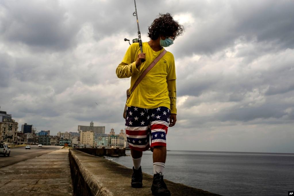 Am Vorabend einer Ausgangssperre geht ein Angler mut Maske an der Mauer des Malecón in Havanna entlang. | Bildquelle: Radio Televisión Martí | Bilder sind in der Regel urheberrechtlich geschützt
